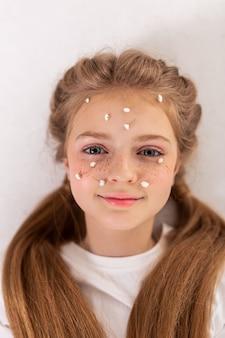 Rosto fofo. simpática e bela jovem com sardas nas faces e rosto coberto por pequenas flores brancas