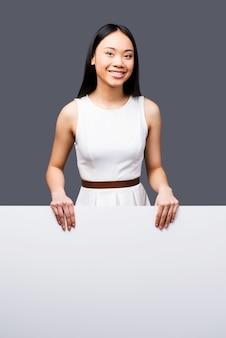 Rosto fresco para um novo projeto. mulher jovem e bonita asiática olhando para a câmera, segurando as mãos no espaço da cópia e sorrindo em pé contra um fundo cinza