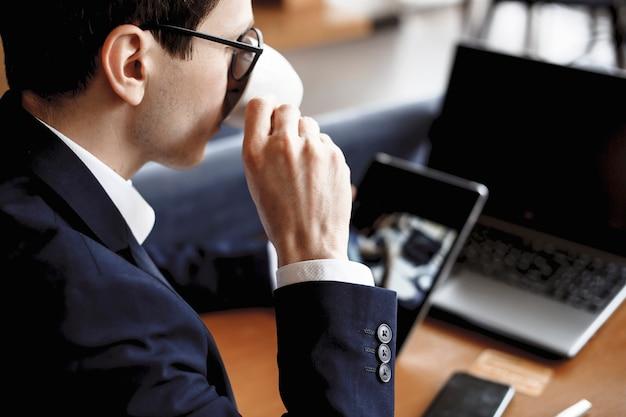 Rosto masculino, bebendo café, segurando um tablet sentado em uma mesa com o laptop nele.