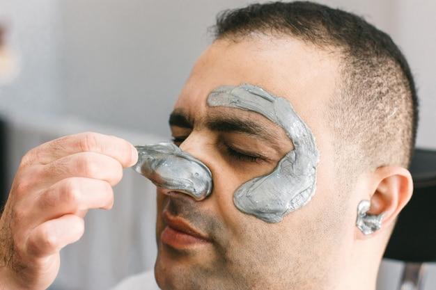 Rosto masculino depilação. o barbeiro remove o cabelo shugaring da cara do homem turco.