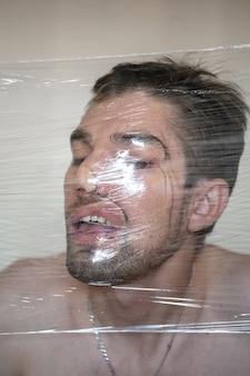 Rosto masculino engraçado, distorção através da embalagem de plástico