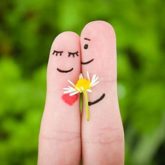 Rosto pintado nos dedos. homem está dando flores para uma mulher.