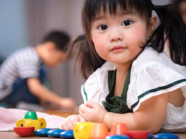 Rosto precioso de uma menina asiática adorável e saudável de 2 anos, deitar no chão e brincar com brinquedos sensoriais coloridos de madeira montessori. pré-escolar menina bonitinha, filha amada, desenvolvimento infantil