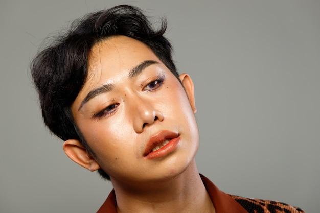Rosto retrato dos anos 20 asiático lgbtqia + cabelo preto de homem gay usa vestido blazzer de capitão. moda masculina apresenta sentimento de emoção sobre fundo cinza isolado