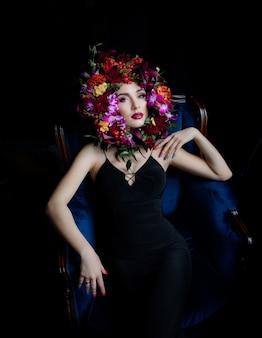 Rosto rodeado de flores coloridas, linda garota vestida de vestido preto na poltrona azul e maquiagem brilhante