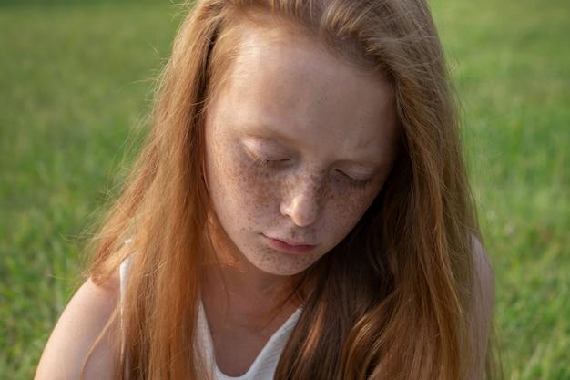 Rosto sombrio de menina triste com sardas com olhos baixos