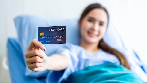 Rosto sorridente de paciente jovem asiático do sexo feminino borrão abstrato com foco no programa segurando um cartão de crédito deitado na cama no quarto do hospital.