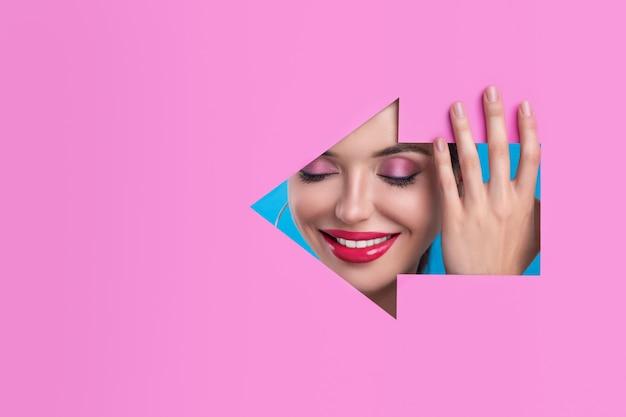 Rosto sorridente de uma bela modelo com maquiagem de olhos brilhantes e lábios cor de rosa brilhantes na figura roxa esculpida sob a forma de uma seta para a esquerda, posando de perfil