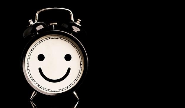 Rosto sorridente dentro do despertador em fundo preto e copie o conceito de espaço, felicidade e mentalidade.
