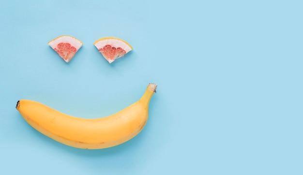Rosto sorridente feito com banana amarela e fatia de laranja sobre fundo azul