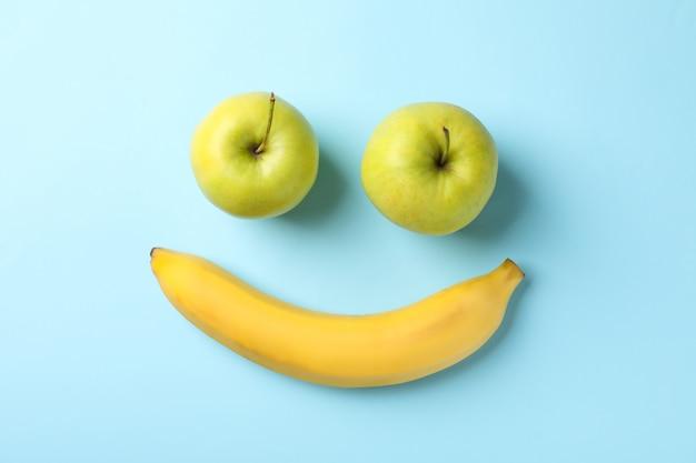 Rosto sorridente feito de bananas e maçãs na mesa azul