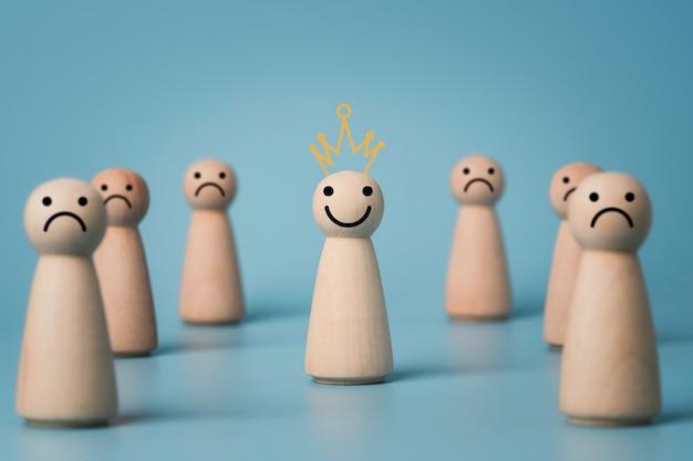 Rosto sorridente na figura de madeira entre a figura de madeira de tristeza sobre fundo azul, conceito de mentalidade e felicidade selecione emoção.