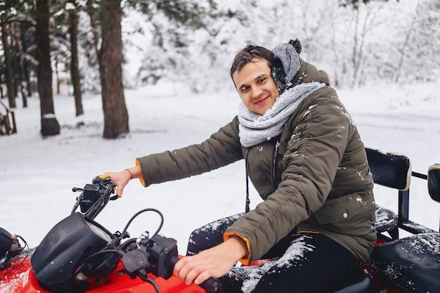 Rosto sorridente na neve e no gelo depois de andar de uma floresta coberta de neve em uma motocicleta
