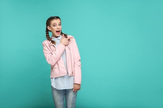 Rosto surpreso apontando o retrato de copyspace da linda linda garota em pé com maquiagem e penteado pigtail na jaqueta rosa de camisa azul listrada. indoor, studio shot isolado em fundo azul ou verde
