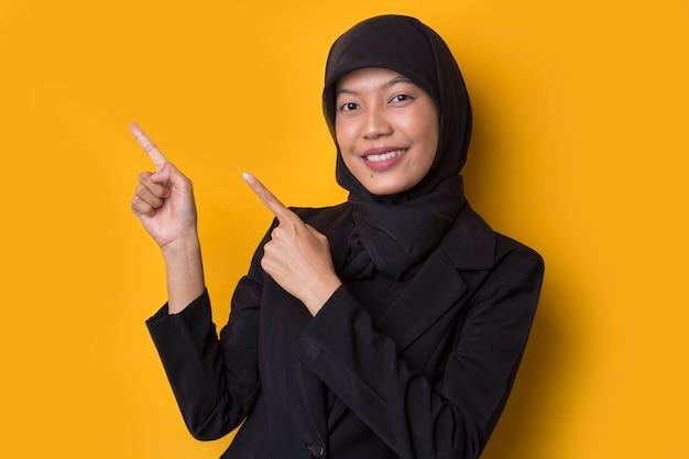 Rosto surpreso de mulher muçulmana asiática com a mão apontando no espaço vazio