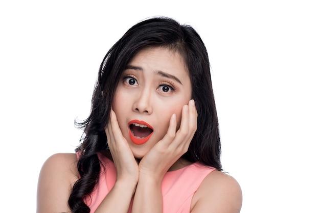 Rosto surpreso de uma jovem mulher asiática sobre branco.