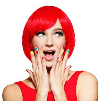 Rosto surpreso de uma jovem mulher bonita com cabelos vermelhos brilhantes e unhas multicoloridas.