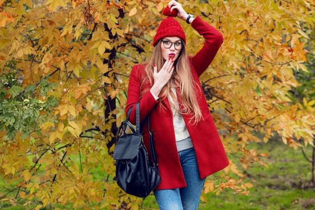 Rosto surpreso. parque de outono. bela moça caminhando e curtindo a natureza.