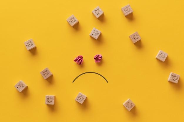 Rosto triste desenhado em um fundo amarelo com muitos blocos de madeira com moléculas covid19 ao redor.