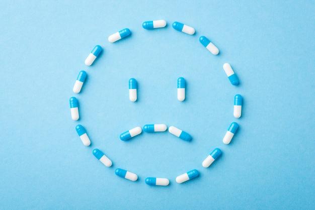 Rosto triste feito de comprimidos em fundo azul