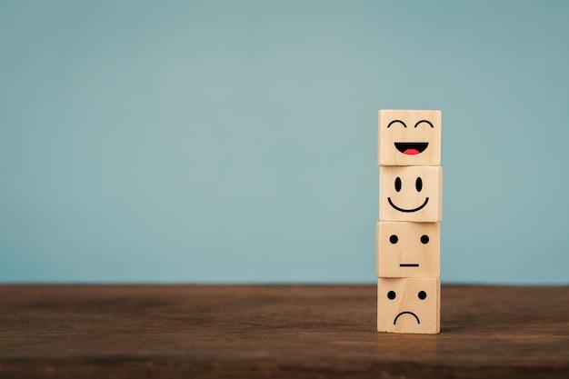 Rostos com emoções diferentes em blocos de madeira empilhados na mesa de madeira e fundo azul