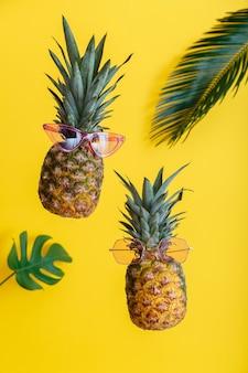 Rostos criativos de abacaxis em óculos de sol coloridos com folhas de palmeira em fundo de verão de cor amarela. frutas tropicais do verão levitando abacaxis.