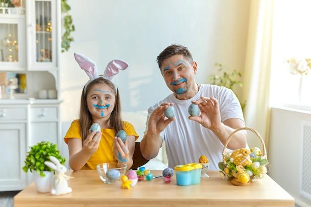 Rostos de pai e filha manchados de tinta azul para pintar ovos. sobre a mesa está uma cesta com ovos de páscoa e tintas.