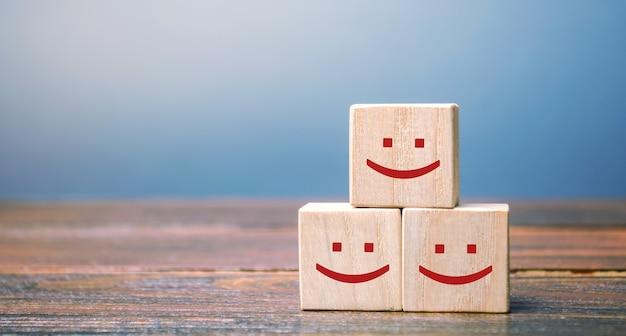 Rostos sorridentes em blocos de madeira.