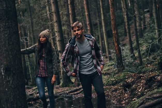 Rota difícil. lindo casal jovem caminhando na floresta enquanto desfruta de sua jornada