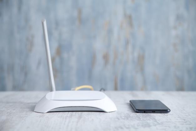 Roteador de internet com smartphone na mesa. tecnologia de rede
