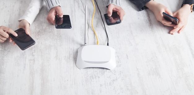 Roteador de internet na mesa. pessoas usando smartphones