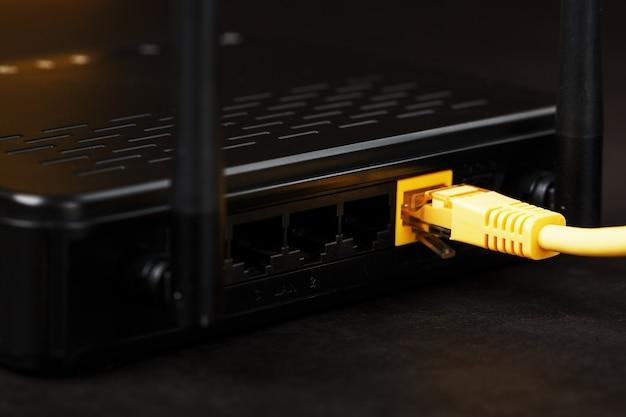 Roteador de modem sem fio com cabo amarelo e porta lan para conexão em um fundo preto.