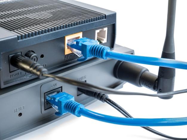 Roteador do internet e ponto de acesso sem fio com o cabo isolado no fundo branco.