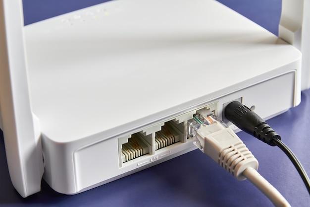 Roteador sem fio branco em fundo azul conectado por cabo à internet