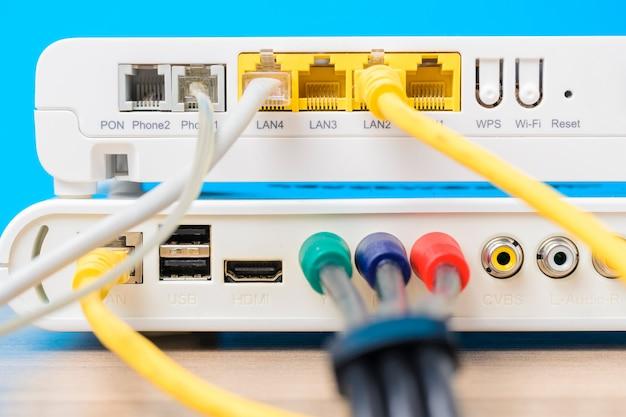 Roteador sem fio em casa com cabos ethernet plugged em fundo azul, close up