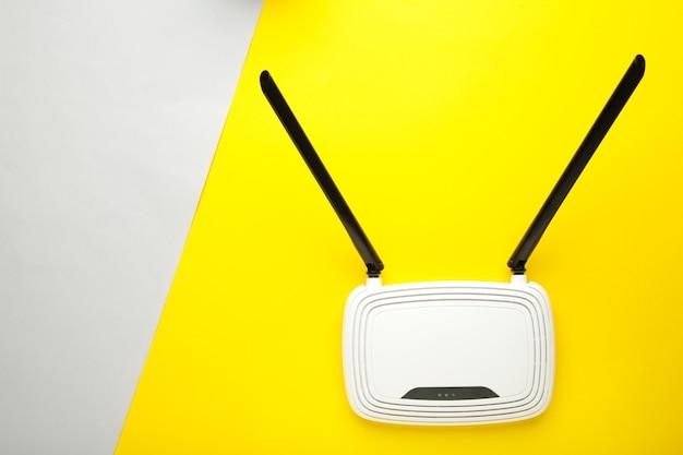 Roteador wi-fi branco com antenas pretas em superfície cinza amarela com espaço de cópia
