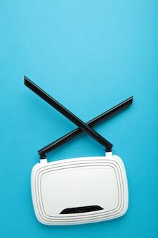 Roteador wi-fi branco com antenas pretas na superfície azul com espaço de cópia