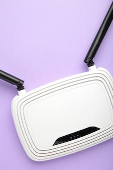 Roteador wi-fi branco com antenas pretas na superfície roxa com espaço de cópia