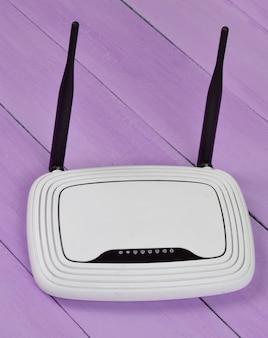 Roteador wi-fi com antenas na mesa de madeira roxa