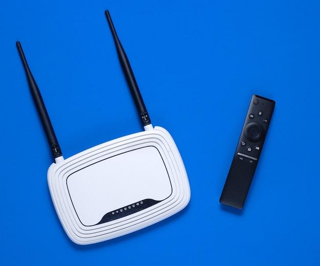 Roteador wi fi, controle remoto da tv em fundo azul