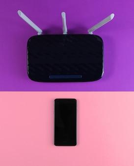 Roteador wi-fi de três antenas com smartphone em papel colorido