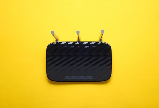 Roteador wi-fi de três antenas preto isolado em amarelo. vista do topo