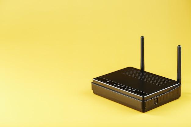 Roteador wifi em preto em um fundo amarelo com espaço livre