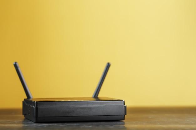 Roteador wifi em preto sobre fundo amarelo com espaço livre.