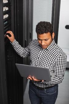 Rotina básica. vista superior de um cara de ti atencioso usando um laptop e tocando o hardware