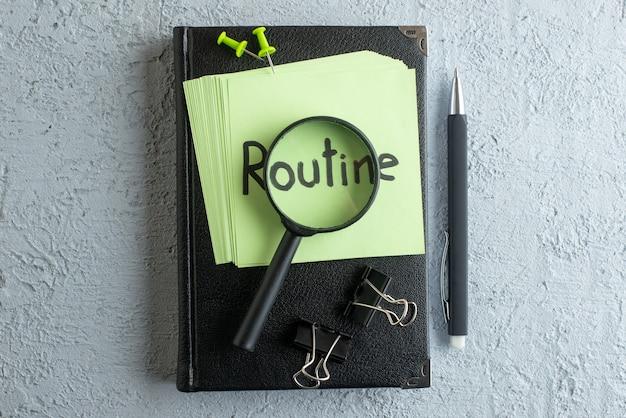 Rotina da vista superior nota escrita em adesivos verdes com bloco de notas e lupa no fundo branco faculdade trabalho escola escritório cor do caderno de negócios