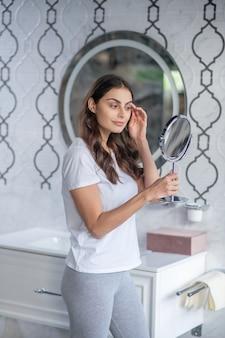 Rotina de autocuidado. uma jovem olhando para o pequeno espelho