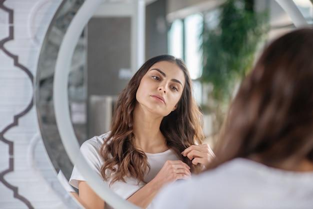 Rotina de beleza. uma mulher verificando as pontas do cabelo perto do espelho