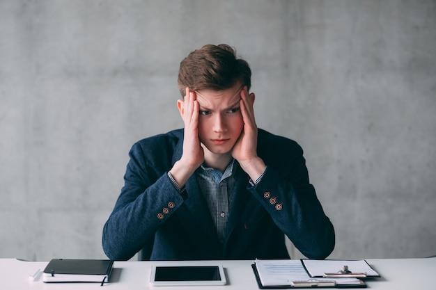 Rotina de escritório e prazos. retrato de estressado jovem gerente sentado na mesa do escritório. copie o espaço.