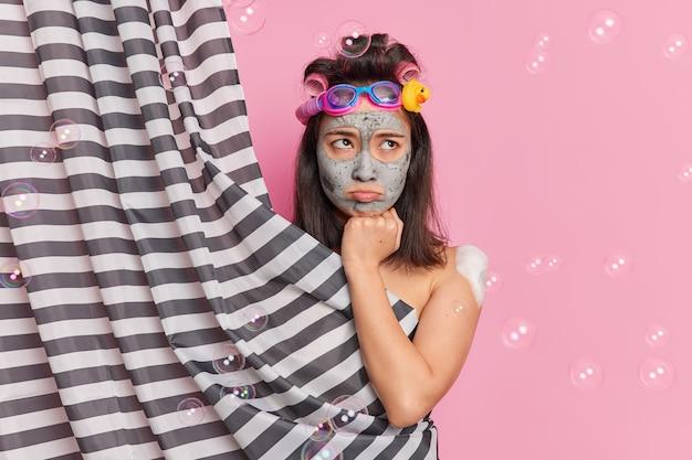 Rotina de manhã e conceito de higiene. jovem morena descontente mulher asain aplica máscara de argila no rosto passa por procedimentos de beleza toma poses de banho atrás de uma cortina isolada sobre fundo rosa
